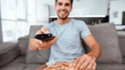 Mouse Infestation man eating pizza and watching tv on sofa